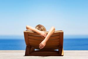 sentada na cadeira em frente ao mar