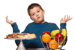 criança em dúvida entre comer um doce ou uma fruta