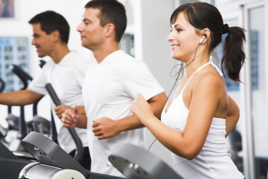 Young adults using running machine at the fitness club