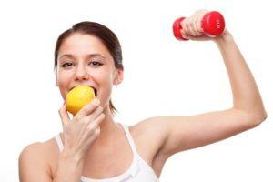 mulher se alimenta com uma fruta e faz exercício com peso