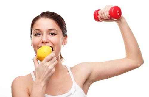 mulher se alimenta com uma fruta e faz exercício com peso para reduzir a perda de massa muscular